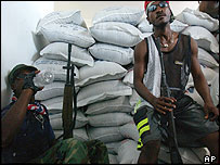Rebels sit by sacks of food in Gonaives