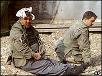 Wounded Iranians sit at the site of a massive train explosion in Neyshabur, Iran on Wednesday