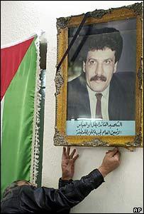 A supporter adjusts a portrait of Abu Abbas before a memorial service in Baghdad