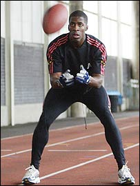 Dwain Chambers catches an American football