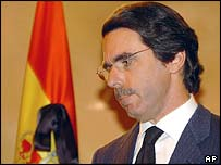 Spanish Prime Minister Jose Maria Aznar in front of a flag bedecked with a mourning ribbon