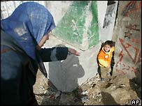 A Palestinian woman beckons to her son after scaling the barrier