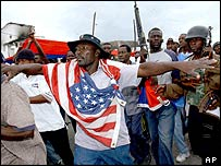 A rebel wearing a US flag takes part in a rally in Gonaives