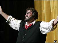 Luciano Pavarotti waves to the audience during the curtain call of Puccini's Tosca at the Metropolitan Opera in New York