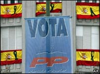 Afiche electoral, sobre un fondo de banderas españolas con lazo negro