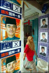 Woman walks past election campaign posters of Malaysian Prime Minister Abdullah Ahmad Badawi