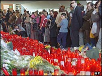 People observe the tributes laid at El Pozo train station in Madrid