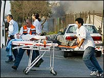 Medical personnel carry a wounded person away from the scene of an attack in the southern Israeli port city of Ashdod