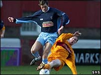 Gordon Greer is tackled by Motherwell's David Clarkson
