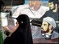 Iranian woman makes a telephone call in front of a revolutionary mural in Tehran