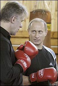 Vladimir Putin (right) dons boxer's gloves speaking with Vyacheslav Fetisov, Chairman of Russia's State Sports Committee in Moscow on Sunday