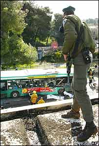 Israeli soldier looks down on scene of bombing