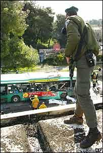 Israeli soldier looks down on scene of bombing