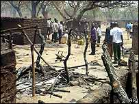 People walk around the remains of the camp in Lira