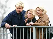 Paul Dowdall, friend, Sue Norman and Beverley Little look over the motorway footbridge on the M3 near Camberley where Mr Little died.