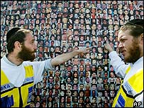 Ultra-Orthodox rescue workers point out the faces of victims of suicide bombings in a display in east Jerusalem