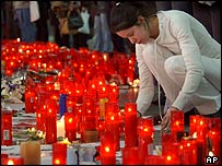 A girl lights a candle in memory of the victims at Atocha station