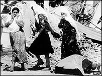 Palestinian women walk past a victim of the 1982 massacre in the Sabra refugee camp in southern Lebanon