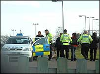 Arrested protesters being led away from the Caterpillar Perkins plant in Shrewsbury