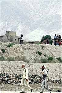 Pakistani tribesmen walk past a Pakistani soldier on the border with Afghanistan