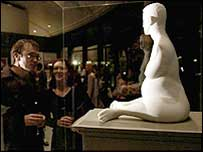 Gallery-goers look at a model of the sculpture