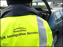 An immigration officer searches a car