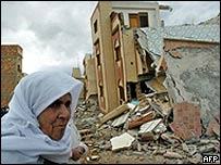 A woman walks past a collapsed building in Imzouren