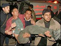 Palestinians carry a man wounded in the first Israeli air force missile strike on the Rafah refugee camp