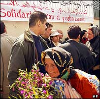 A woman holds flowers as hundreds of Moroccans show support for victims of the Madrid train bombings