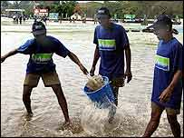 Groundstaff work to clear away surface water from the covers
