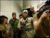 A US soldiers shows Iraqi troops how to search a house