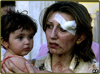 An injured woman holds a child at Ibn Al-Nafees hospital after the bomb blasts in Baghdad
