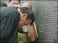 German Chancellor Gerhard Schroeder, bows in front of a memorial wall in Warsaw