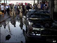 Iraqis crowd around US soldiers guarding the scene after a bomb blast in front of a Christian church in Baghdad, 1 August 2004