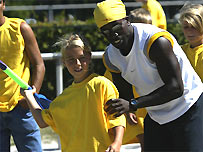 A coach guides a young athlete in the javelin