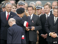 A survivor of the uprising salutes in front of German Chancellor Gerhard Schroeder