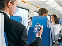 Man holding Blackberry on train