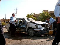 Police at the damaged car of a police chief killed on Tuesday