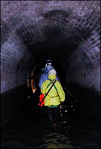 Group walking in sewage tunnel