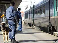 A policeman with a dog stands on a platform at Toulouse-Matabiau station