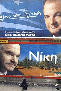 A pedestrian passes huge posters of New Democracy leader Costas Karamanlis (top) and Pasok leader George Papandreou