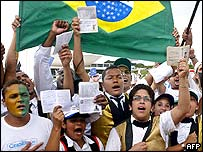 Bingo staff wave their workers books during a march in Brasilia