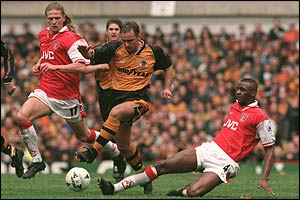 Wolves' Paul Simpson is overpowered by Petit and Vieira
