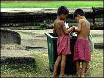 Street children search a rubbish bin for food