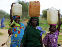 Sudanese refugees carry water containers on their head, Chad