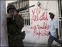 US marine in Haiti, in front of graffiti reading Long live Aristide