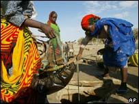 Refugees from Darfur pump water across the border in Chad