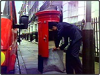 Postman collecting mail from a post box
