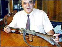 The director of Albania's National Historical Museum shows the rifle used by Italian guerrillas to execute Mussolini