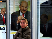 Woman at bus stop in Athens surrounded by posters of George Papandreou